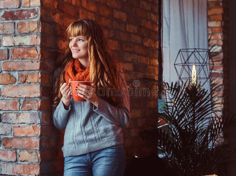 Πορτρέτο ενός μόνου redhead κοριτσιού που φορά ένα θερμό πουλόβερ που κρατά ένα φλιτζάνι του καφέ κλίνοντας σε έναν τουβλότοιχο στοκ εικόνες