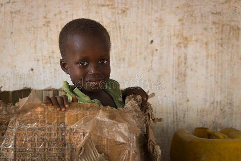 Πορτρέτο ενός νέου αγοριού που παίζει σε ένα κιβώτιο καρτών στην πόλη Nhacra στη Γουινέα-Μπισσάου στοκ εικόνα