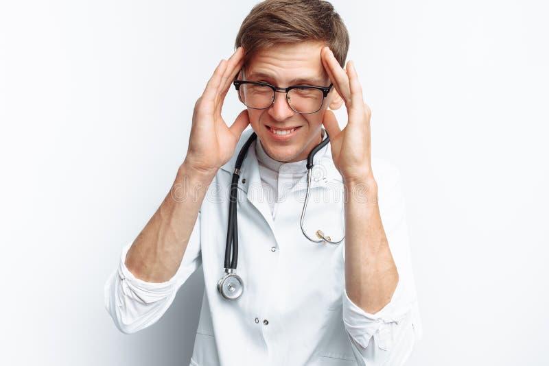 Πορτρέτο ενός νέου γιατρού, σε ένα άσπρο υπόβαθρο, το οποίο απεικονίζει έναν πονοκέφαλο, εκπαιδευόμενος στο στούντιο, με ένα στηθ στοκ φωτογραφίες