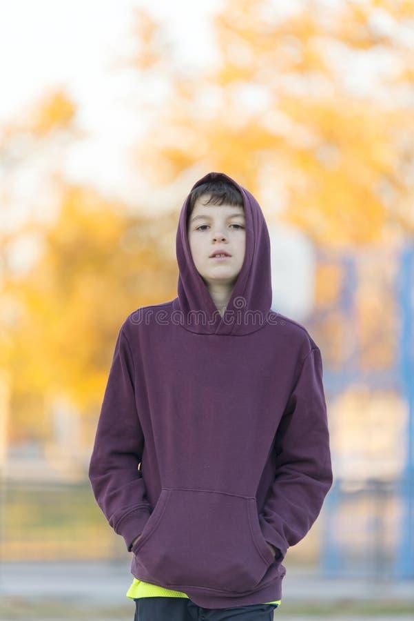 Πορτρέτο ενός νέου ελκυστικού αγοριού στην κόκκινη κουκούλα υπαίθρια στοκ εικόνες