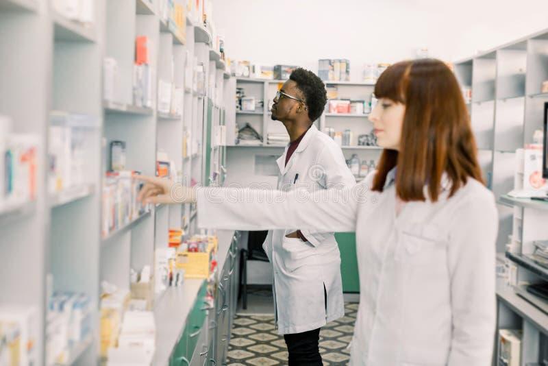 Πορτρέτο ενός νέου καυκάσιου θηλυκού φαρμακοποιού, άνδρας αφρικανικός συνάδελφος που εργάζεται με τα φάρμακα στο υπόβαθρο Εστίαση στοκ φωτογραφίες με δικαίωμα ελεύθερης χρήσης