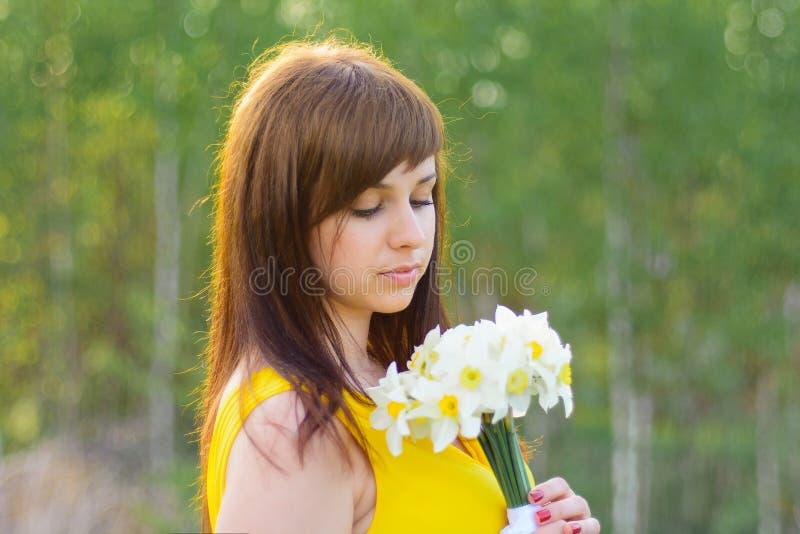 Πορτρέτο ενός νέου κοριτσιού με μια ανθοδέσμη της άνοιξη daffodils στοκ φωτογραφία με δικαίωμα ελεύθερης χρήσης