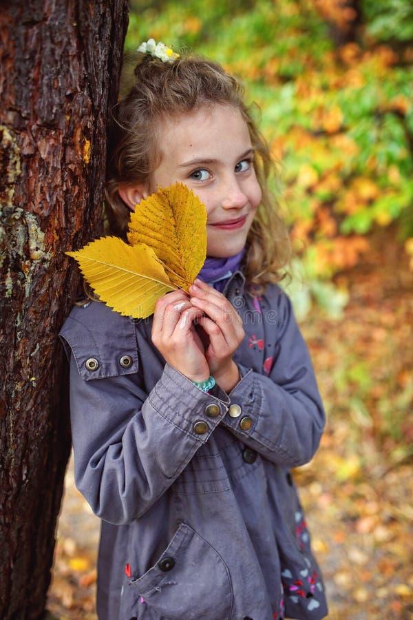 Πορτρέτο ενός νέου κοριτσιού με τα φύλλα φθινοπώρου στοκ φωτογραφία