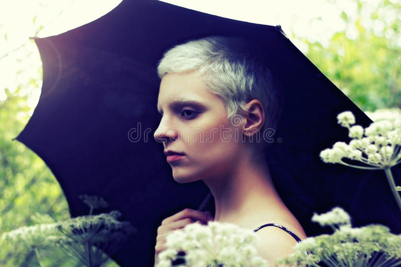 Πορτρέτο ενός νέου ξανθού κοριτσιού με μια ομπρέλα στο λιβάδι στοκ εικόνες με δικαίωμα ελεύθερης χρήσης