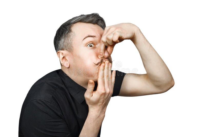 Πορτρέτο ενός νέου τύπου με την γκρίζα τρίχα με το αίσθημα άρρωστος, το οποίο καλύπτει το στόμα και τη μύτη του από τη δυσωδία με στοκ εικόνες