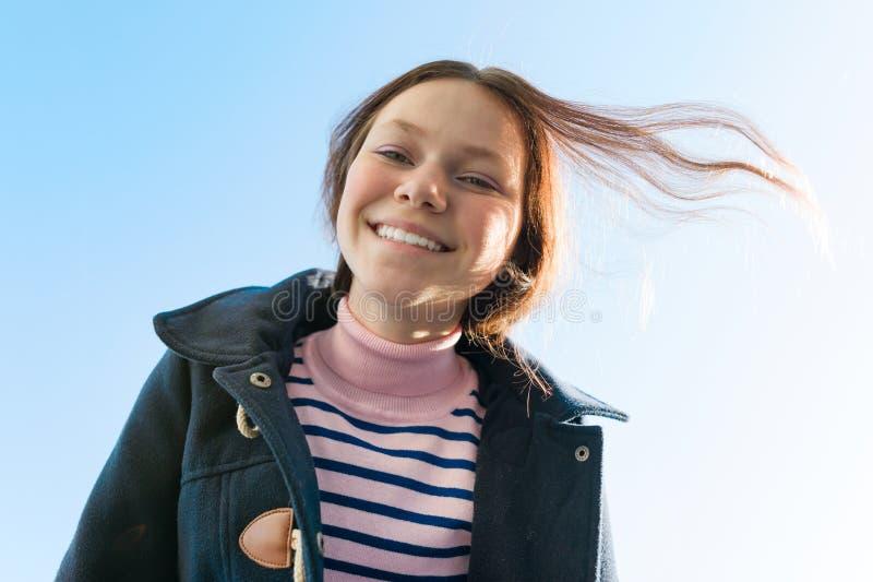Πορτρέτο ενός νέου χαμογελώντας κοριτσιού εφήβων, μπλε ουρανός υποβάθρου στοκ φωτογραφία