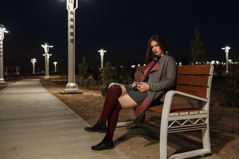 Πορτρέτο ενός νέου όμορφου κοριτσιού brunette στις γυναικείες κάλτσες γκρίζων παλτών και Burgundy που κάθεται σε έναν πάγκο με μι στοκ εικόνες