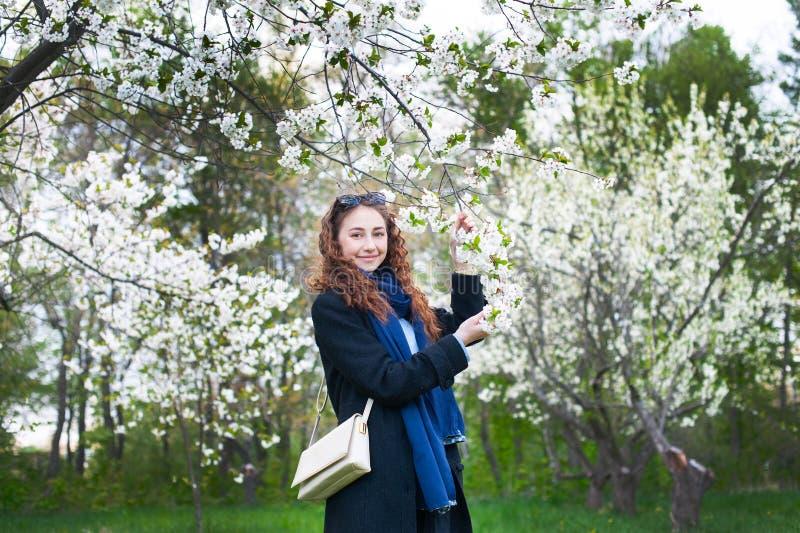 Πορτρέτο ενός νέου όμορφου μοντέρνου πάρκου γυναικών ανθίζοντας την άνοιξη Ευτυχής τοποθέτηση κοριτσιών σε έναν ανθίζοντας κήπο μ στοκ εικόνα με δικαίωμα ελεύθερης χρήσης