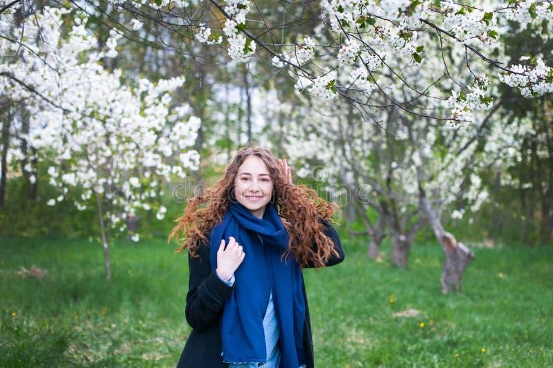 Πορτρέτο ενός νέου όμορφου μοντέρνου πάρκου γυναικών ανθίζοντας την άνοιξη Ευτυχής τοποθέτηση κοριτσιών σε έναν ανθίζοντας κήπο μ στοκ φωτογραφία με δικαίωμα ελεύθερης χρήσης