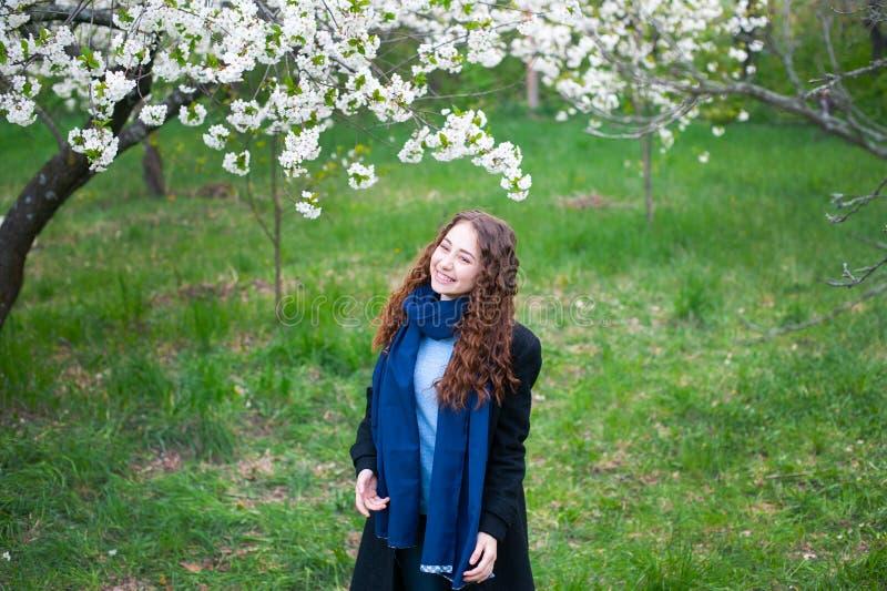 Πορτρέτο ενός νέου όμορφου μοντέρνου πάρκου γυναικών ανθίζοντας την άνοιξη Ευτυχής τοποθέτηση κοριτσιών σε έναν ανθίζοντας κήπο μ στοκ εικόνες