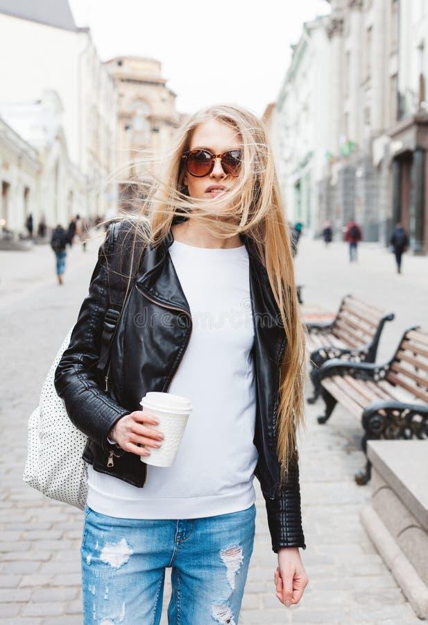 Πορτρέτο ενός νέου όμορφου ξανθού κοριτσιού με τα γυαλιά ηλίου που περπατά στις οδούς της Ευρώπης με τον καφέ Ο αέρας που φυσά το στοκ φωτογραφία με δικαίωμα ελεύθερης χρήσης