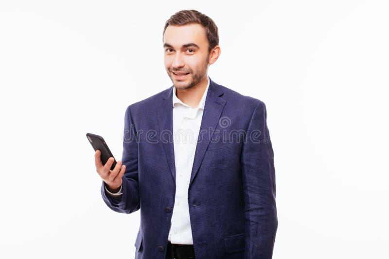 Πορτρέτο ενός νεαρού άνδρα με μια γενειάδα σε ένα ελεγμένο πουκάμισο, που χρησιμοποιεί το smartphone, που χαμογελά σε ένα άσπρο υ στοκ εικόνα με δικαίωμα ελεύθερης χρήσης