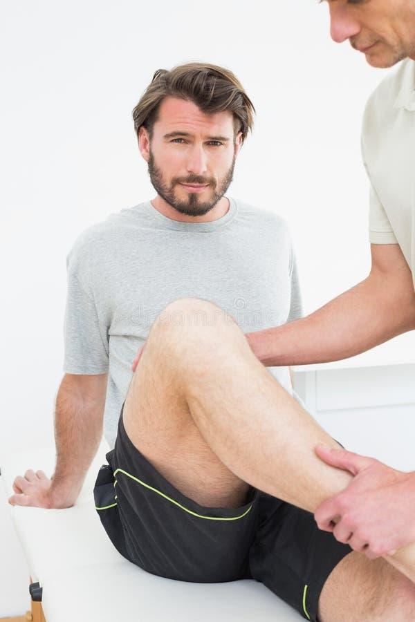 Πορτρέτο ενός νεαρού άνδρα που παίρνει το γόνατό του εξετασμένο στοκ φωτογραφίες