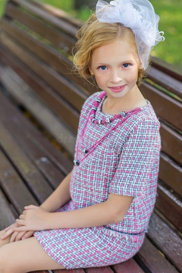 Πορτρέτο ενός ξανθού στη ρόδινη ενδυμασία σε ένα πάρκο υπαίθρια στοκ εικόνες