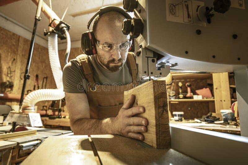 Πορτρέτο ενός ξυλουργού μέσα στο εργαστήριο ξυλουργικής του που χρησιμοποιεί ένα πριόνι ζωνών στοκ φωτογραφίες με δικαίωμα ελεύθερης χρήσης