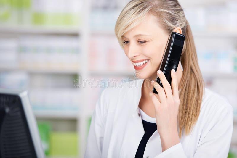 Πορτρέτο ενός φιλικού φαρμακοποιού στο τηλέφωνο στοκ εικόνα