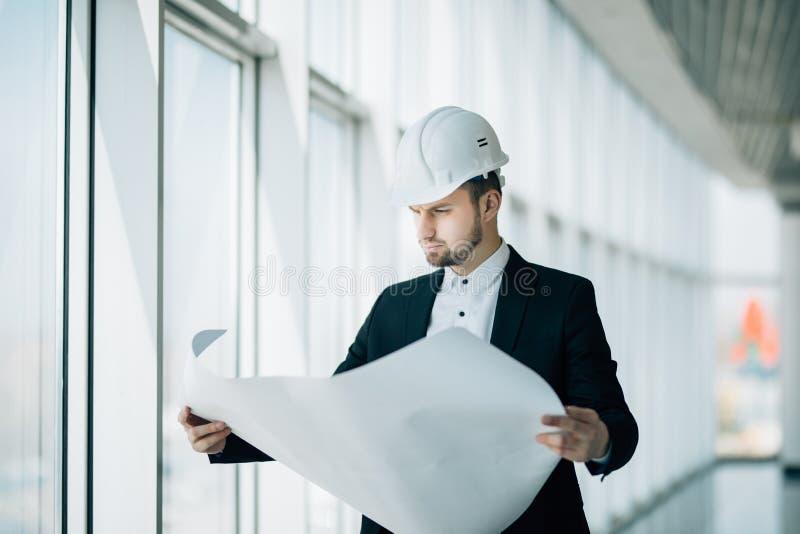 Πορτρέτο ενός χαμογελώντας αρσενικού μηχανικού αναδόχων με το σκληρό σχεδιάγραμμα ανάγνωσης καπέλων στο εργοτάξιο οικοδομής στοκ φωτογραφίες με δικαίωμα ελεύθερης χρήσης