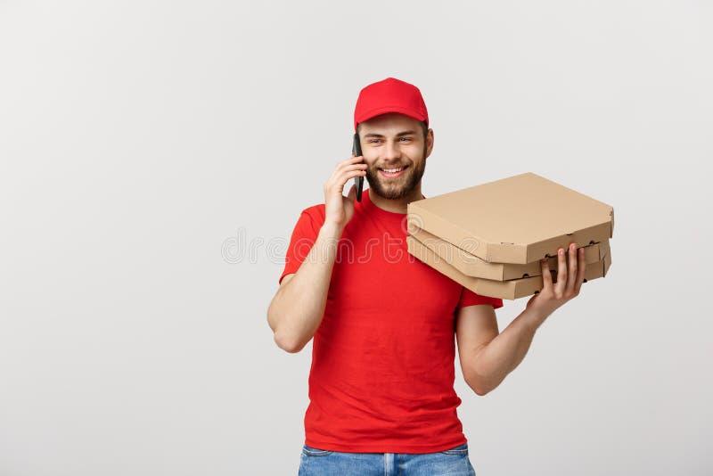 Πορτρέτο ενός χαμογελώντας ατόμου παράδοσης στην κόκκινη ΚΑΠ που μιλά στο κινητό τηλέφωνο κρατώντας τα κιβώτια πιτσών απομονωμένα στοκ εικόνες