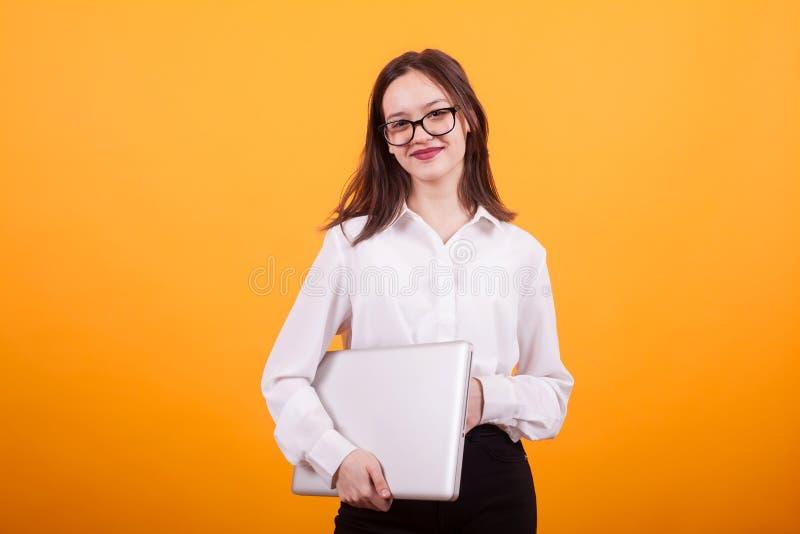 Πορτρέτο ενός χαμογελώντας θηλυκού εφήβου που στέκεται με το lap-top στα χέρια της πέρα από το κίτρινο υπόβαθρο στοκ φωτογραφίες με δικαίωμα ελεύθερης χρήσης