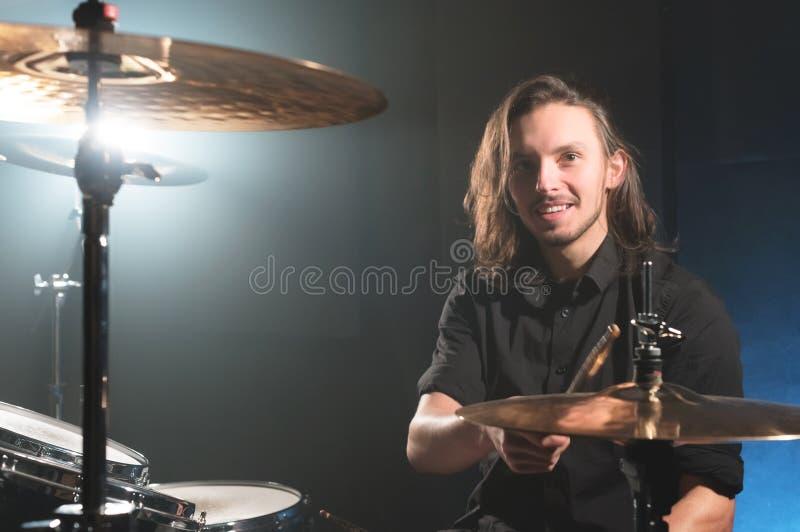 Πορτρέτο ενός χαμογελώντας μακρυμάλλους τυμπανιστή με chopsticks στα χέρια του που κάθεται πίσω από ένα σύνολο τυμπάνων Συγκρατημ στοκ εικόνες
