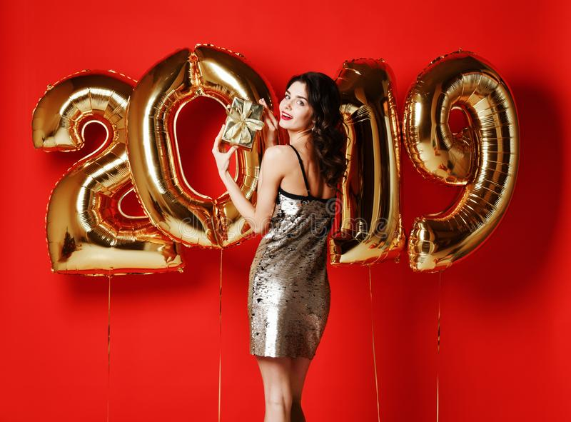 Πορτρέτο ενός χαμογελώντας νέου έκπληκτου κοριτσιού στο χρυσό λαμπρό φόρεμα που παρουσιάζει κιβώτιο δώρων και που εξετάζει τη κάμ στοκ εικόνες με δικαίωμα ελεύθερης χρήσης