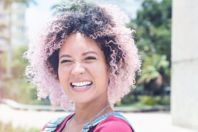 Πορτρέτο ενός χαμογελώντας πανκ κοριτσιού με τη ρόδινη τρίχα στοκ φωτογραφίες