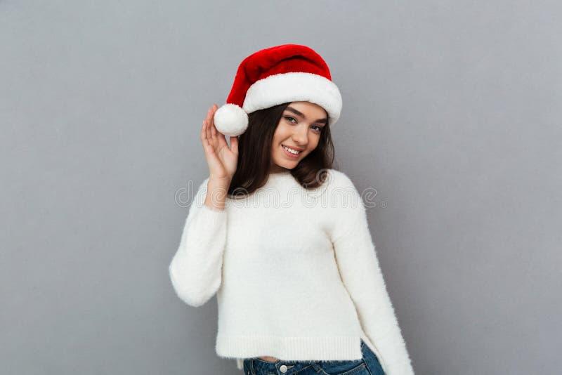 Πορτρέτο ενός χαμογελώντας όμορφου κοριτσιού που φορά το κόκκινο καπέλο santa στοκ φωτογραφίες