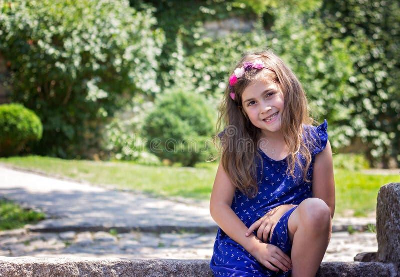 Πορτρέτο ενός χαμογελώντας όμορφου μικρού κοριτσιού στο μπλε φόρεμα, στο θόριο στοκ φωτογραφίες με δικαίωμα ελεύθερης χρήσης
