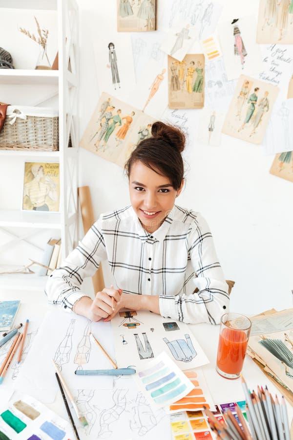 Πορτρέτο ενός χαμογελώντας θηλυκού σχεδιαστή μόδας που δημιουργεί τα σκίτσα στοκ φωτογραφία με δικαίωμα ελεύθερης χρήσης