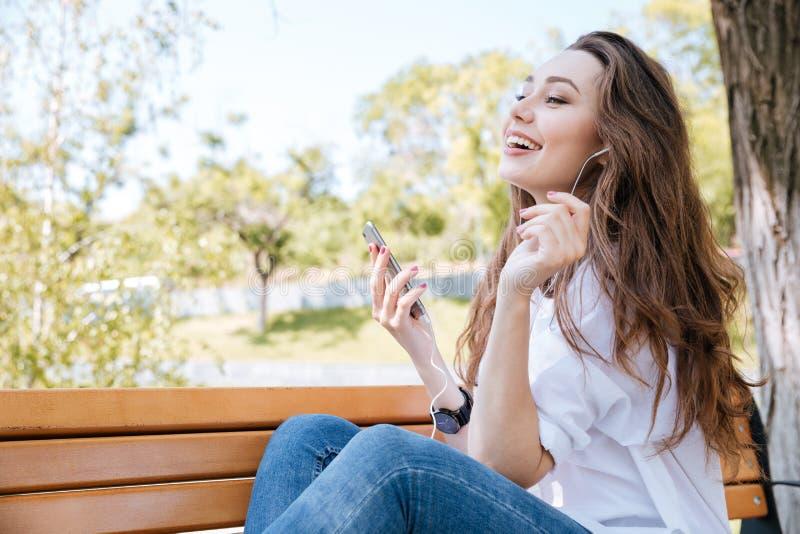 Πορτρέτο ενός χαμογελώντας κοριτσιού με τη μουσική ακούσματος ακουστικών υπαίθρια στοκ εικόνες