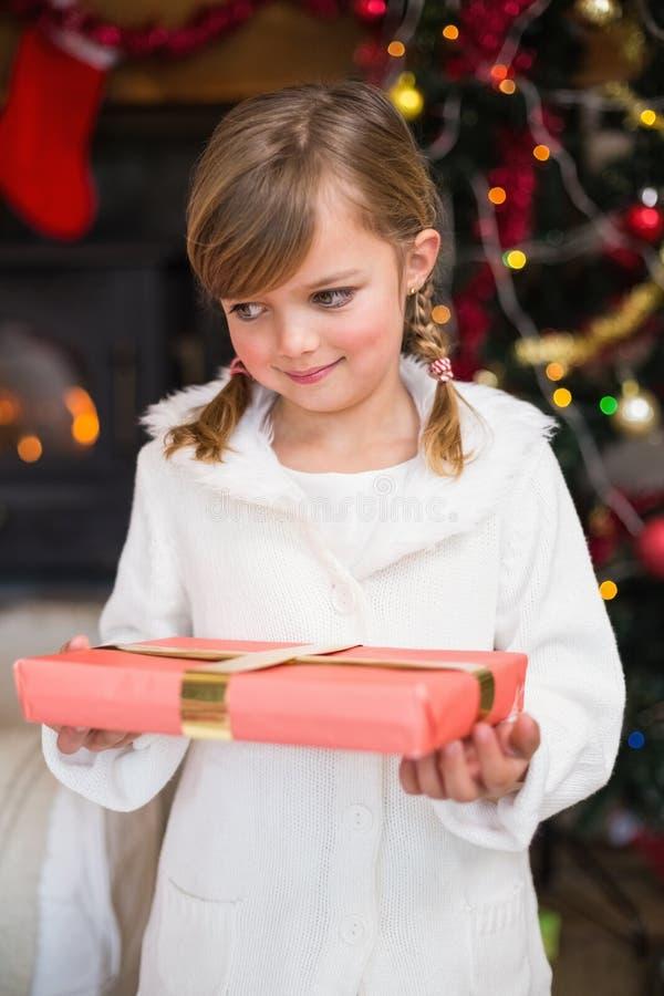 Πορτρέτο ενός χαμογελώντας μικρού κοριτσιού που κρατά ένα τυλιγμένο δώρο στοκ φωτογραφία