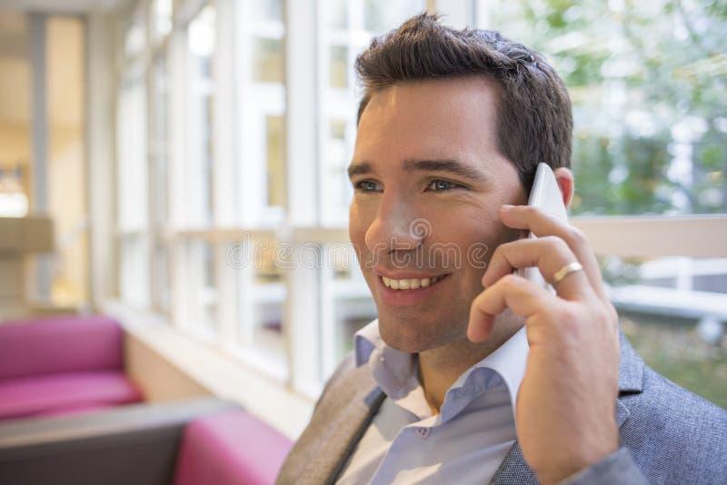 Πορτρέτο ενός χαμογελώντας νέου επιχειρηματία που χρησιμοποιεί το κινητό τηλέφωνο στον καναπέ, στοκ φωτογραφία με δικαίωμα ελεύθερης χρήσης