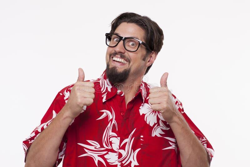 Πορτρέτο ενός χαμογελώντας νεαρού άνδρα που παρουσιάζει αντίχειρες ενάντια στο λευκό στοκ εικόνες