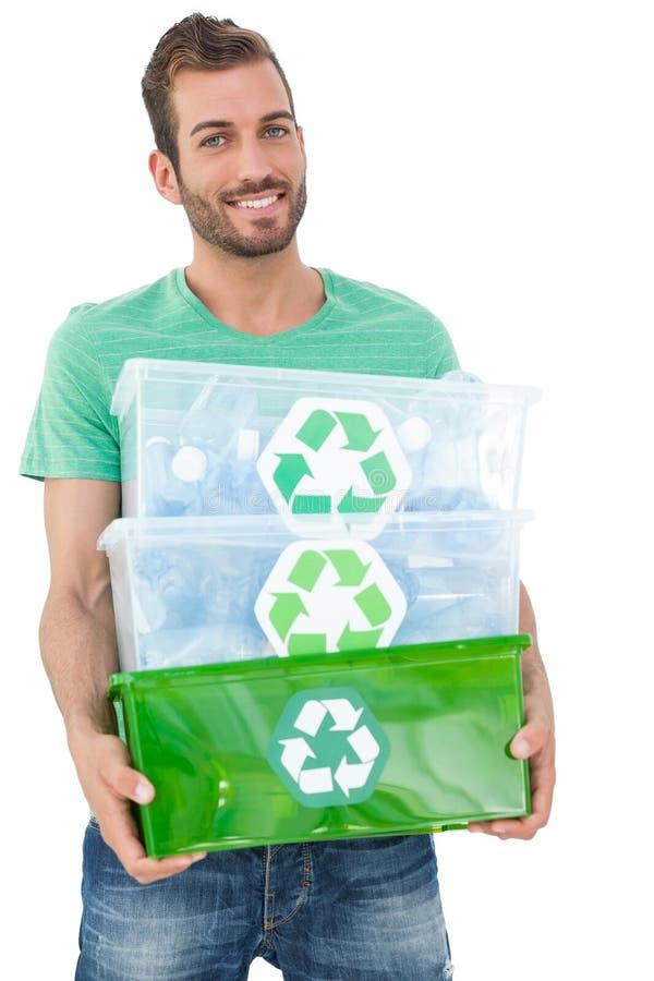Πορτρέτο ενός χαμογελώντας νεαρού άνδρα που φέρνει τα ανακύκλωσης εμπορευματοκιβώτια στοκ φωτογραφίες