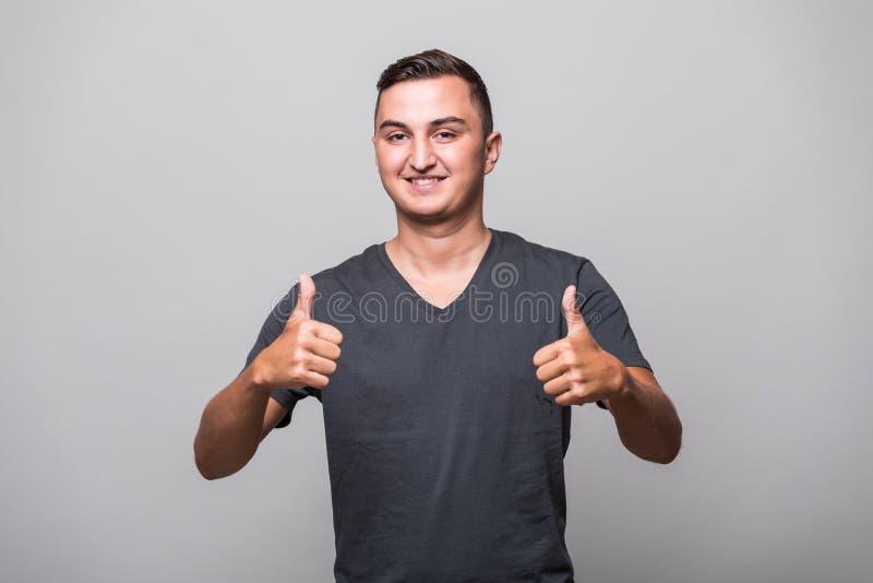 Πορτρέτο ενός χαμογελώντας περιστασιακού ατόμου που παρουσιάζει δύο αντίχειρες και που εξετάζει τη κάμερα στοκ φωτογραφία με δικαίωμα ελεύθερης χρήσης