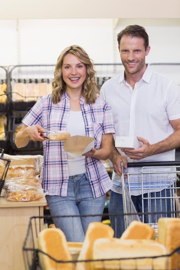 Πορτρέτο ενός χαμογελώντας περιστασιακού ζεύγους που παίρνει ένα ψωμί στοκ φωτογραφίες με δικαίωμα ελεύθερης χρήσης