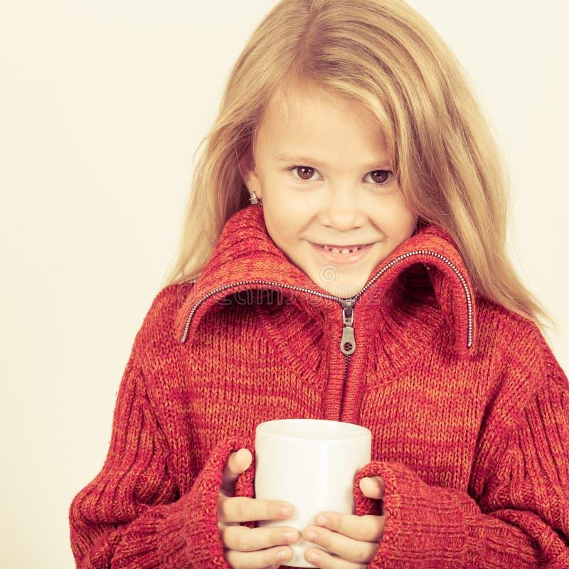 Πορτρέτο ενός χαριτωμένου μικρού κοριτσιού στο κόκκινο πουλόβερ που κρατά μια κούπα στοκ εικόνες