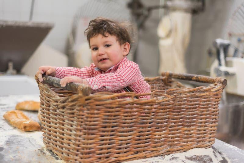 Πορτρέτο ενός χαριτωμένου μωρού μέσα σε ένα καλάθι με το ψωμί στο αρτοποιείο στοκ εικόνα