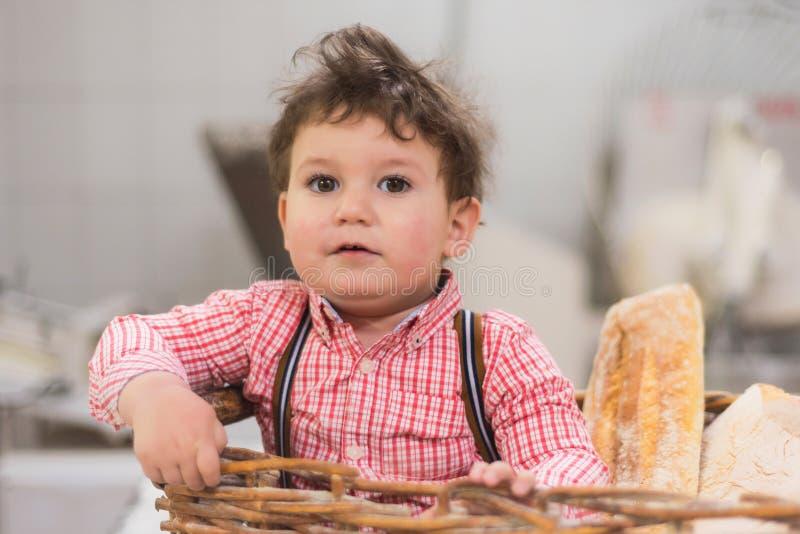 Πορτρέτο ενός χαριτωμένου μωρού μέσα σε ένα καλάθι με το ψωμί στο αρτοποιείο στοκ εικόνες