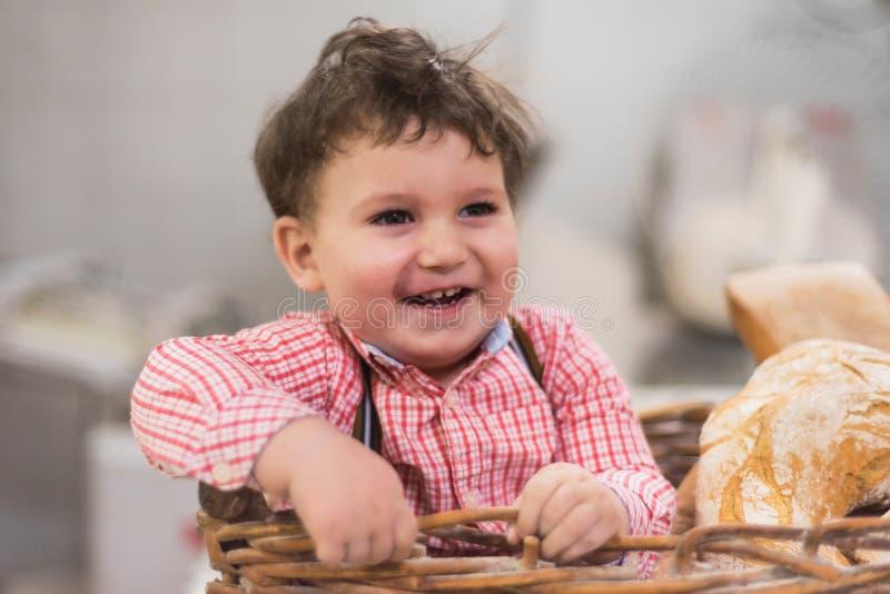 Πορτρέτο ενός χαριτωμένου μωρού μέσα σε ένα καλάθι με το ψωμί στο αρτοποιείο στοκ φωτογραφία