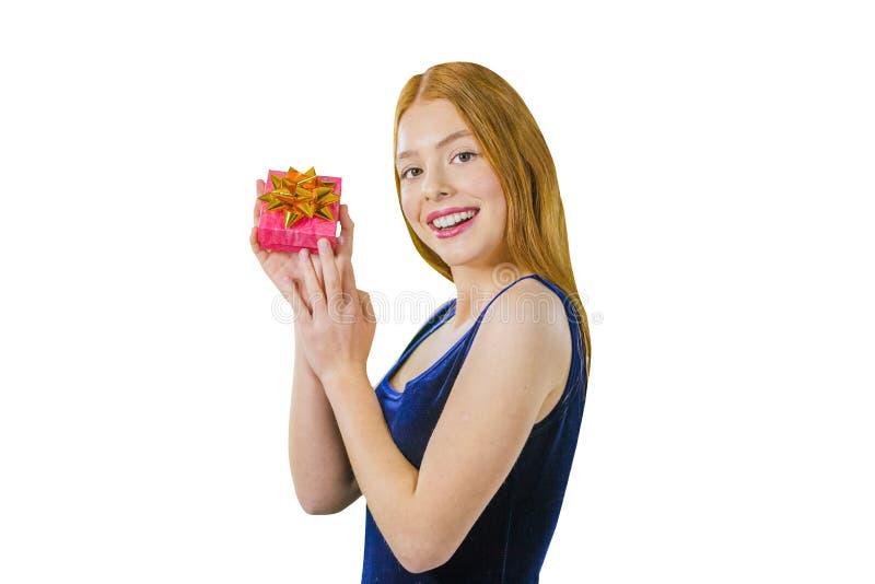 Πορτρέτο ενός χαριτωμένου νέου κοκκινομάλλους κοριτσιού που στέκεται μισή στροφή και κρατά ένα μικρό κιβώτιο με ένα δώρο κοντά στ στοκ εικόνα με δικαίωμα ελεύθερης χρήσης