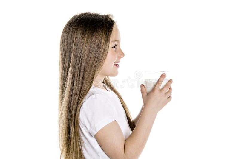 Πορτρέτο ενός χαριτωμένου χρονών κοριτσιού 7 που απομονώνεται πέρα από το άσπρο υπόβαθρο με το γυαλί γάλακτος στοκ φωτογραφία με δικαίωμα ελεύθερης χρήσης