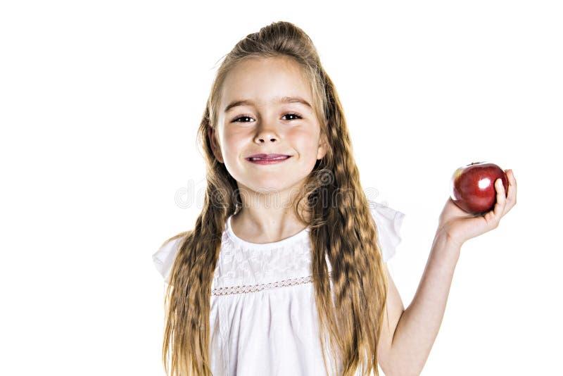 Πορτρέτο ενός χαριτωμένου χρονών κοριτσιού 7 που απομονώνεται πέρα από το άσπρο υπόβαθρο με το μήλο στοκ εικόνα