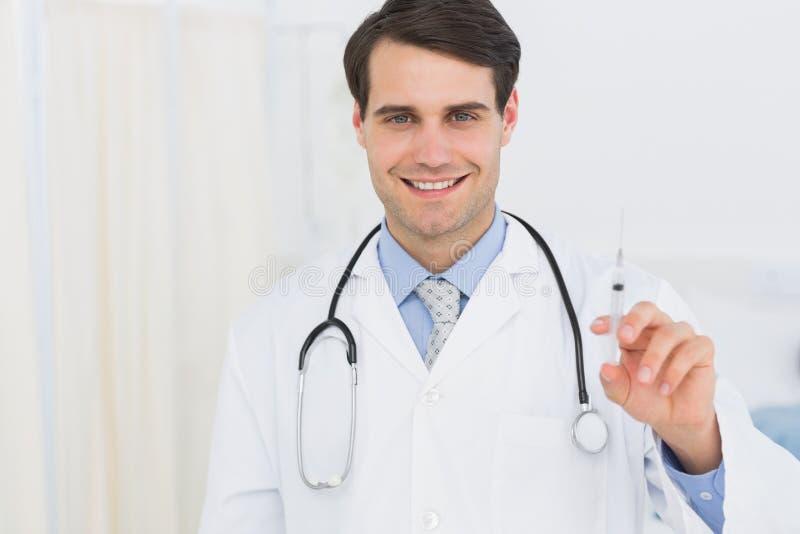 Πορτρέτο ενός όμορφου γιατρού που κρατά μια έγχυση στοκ φωτογραφίες