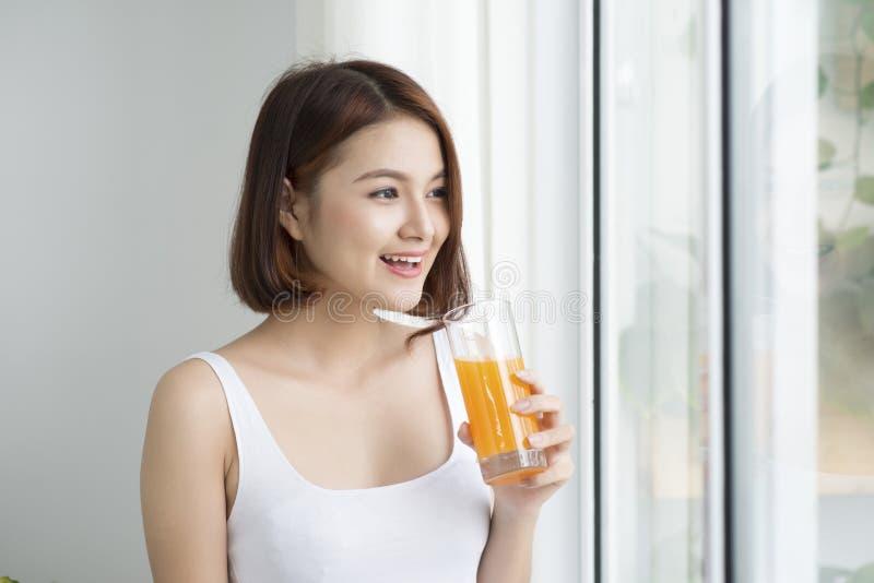 Πορτρέτο ενός όμορφου γυαλιού εκμετάλλευσης γυναικών με το νόστιμο χυμό Υγιεινός τρόπος ζωής, χορτοφάγος διατροφή και γεύμα Πιείτ στοκ εικόνα