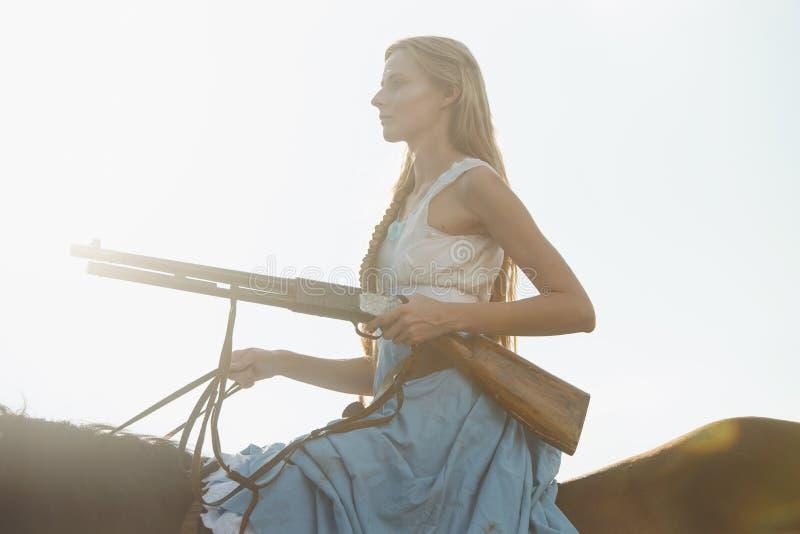 Πορτρέτο ενός όμορφου θηλυκού cowgirl με το κυνηγετικό όπλο από την άγρια δύση που οδηγά ένα άλογο στον εσωτερικό στοκ εικόνες με δικαίωμα ελεύθερης χρήσης