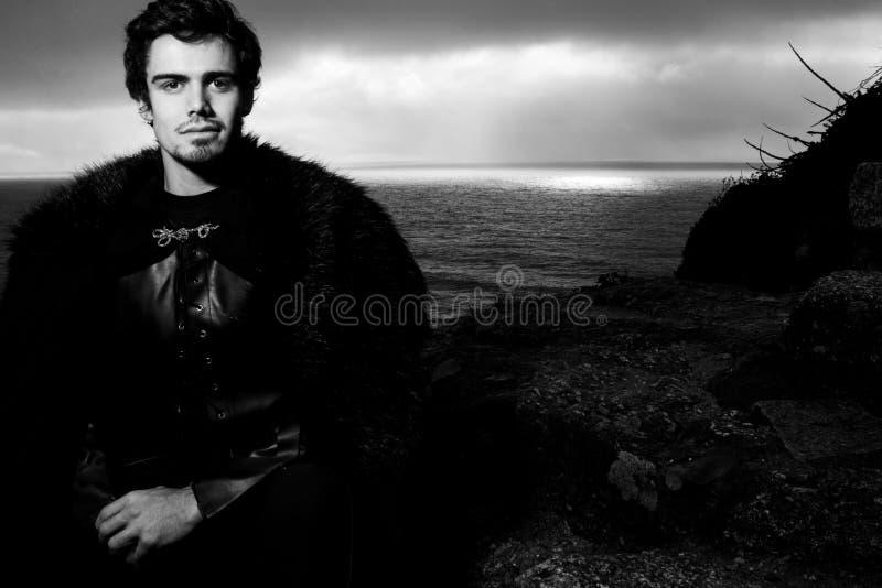 Πορτρέτο ενός όμορφου ιππότη με κατσίκα και γούνα που κοιτάζει την κάμερα με ωκεανούς στο φόντο στοκ εικόνα