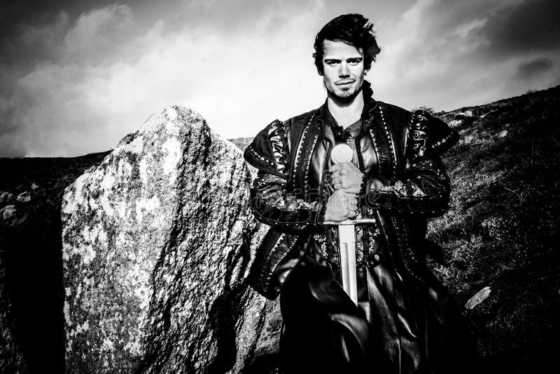 Πορτρέτο ενός όμορφου ιππότη που στέκεται δίπλα στο σπαθί του ροκ κρατώντας την κάμερα στοκ φωτογραφία