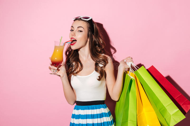 Πορτρέτο ενός όμορφου κοκτέιλ κατανάλωσης νέων κοριτσιών shopaholic στοκ εικόνες
