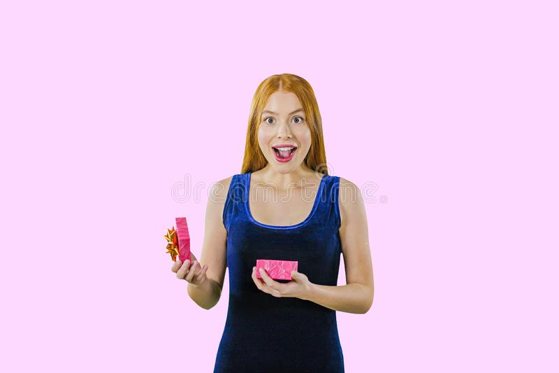 Πορτρέτο ενός όμορφου κοριτσιού με τη μακριά κόκκινη τρίχα που κρατά ένα κιβώτιο με ένα δώρο Το άνοιγμα του καπακιού χαμογελά ενθ στοκ φωτογραφία